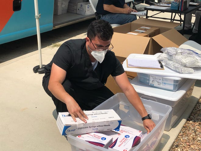 Ricky Lozano, an emergency medical technician, sorts vaccination supplies at a mobile vaccination clinic held in front of the Rocky Ford Public Safety Building, 300 S. Main St., Sunday.