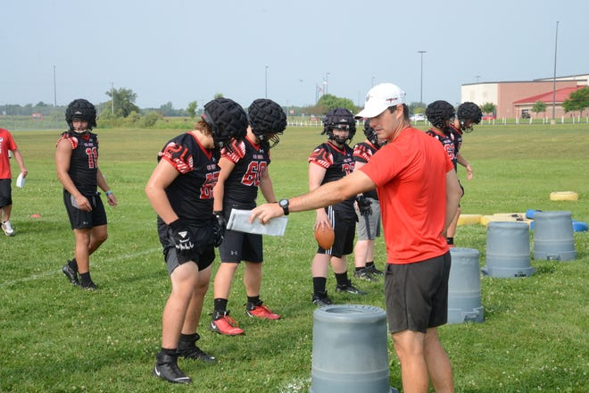 Milan football coach Jesse Hoskins gives instructions during the first day of practice Monday.