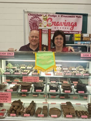 Shaun and Sheila McGowan, owners of Cravings, a sweets and dessert shop that once operated in downtown Monroe, stand behind their exhibit of freshly made chocolates, fudge and cinnamon nut treats at their booth at the Monroe County Fair last week. The popular booth inside the First Merchants Bank Expo Center was picked by judges as the best indoor exhibit at the fair.