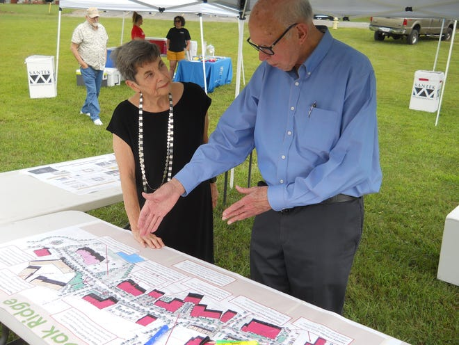 Pat Postma, left, listens to John Rather of Rather Creative Group Inc. share ideas about a future downtown Oak Ridge at Toast the Town. On the table is a map of one possible plan.
