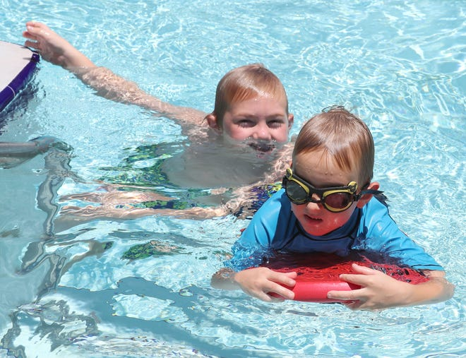 In this file photo from July 2, 2018, Tyler Glickman, 7, left, and his brother, Jordan, 5, right, swim together in the pool at the Silver Springs Shores Community Center pool in Silver Springs Shores, Fla. The community center has reopened after multiple employees tested positive for COVID-19, but the pool is operating under temporary hours due to staffing.
