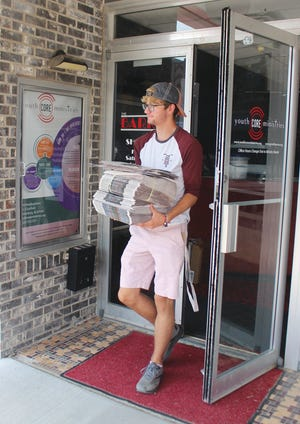 Caleb Powell gathers recyclable papers and takes them to the recycling center as part of his new Eco Pickup business in Pratt.
