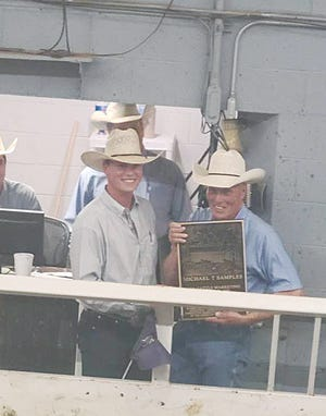 Brian Winter presents Mike Samples (right) with a plaque in honor of his  years marketing cattle for Pratt Livestock and as an inductee in the Cattle Marketing Hall of Fame.