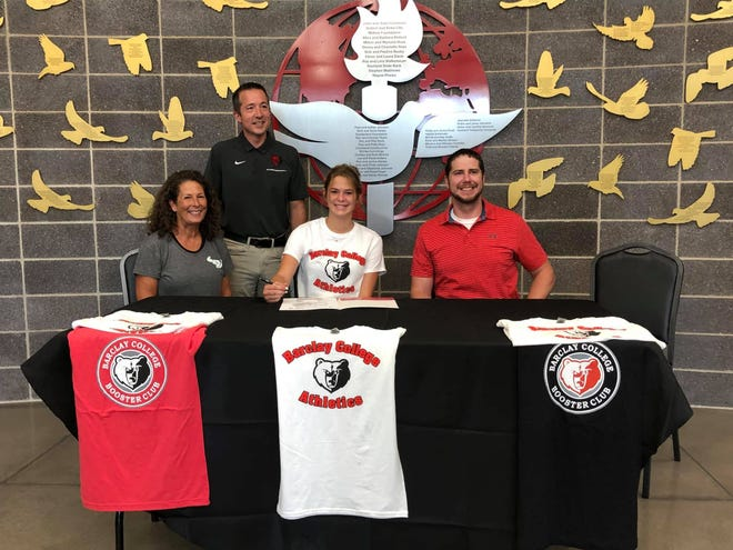Madi Yost, center, signs a letter of intent to particpate in track and field at Barclay College for the coming school year.
