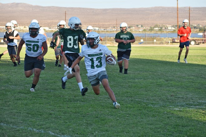 Steven Olmos runs the ball during Burroughs High School's varsity football practice Wednesday.