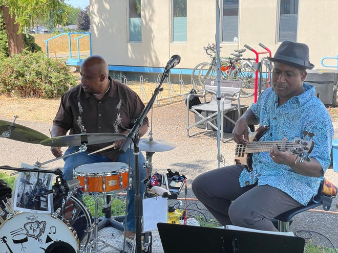 Brothers Edwin Coleman III, left, and Callan Coleman play a song at the mural celebration and picnic at the Dr. Edwin Coleman Jr. Community Center, named after their father.
