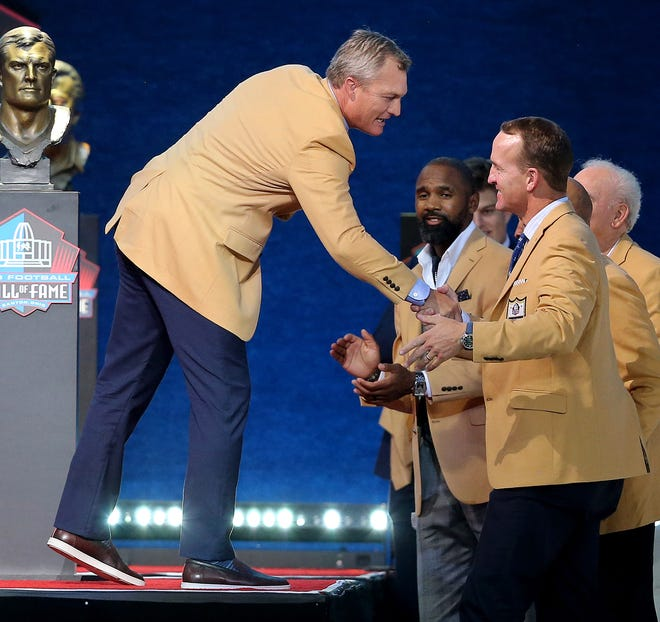 John Lynch shakes hands with Hall of Fame classmate Peyton Manning at the conclusion of his enshrinement speech to the Pro Football Hall of Fame at Tom Benson Hall of Fame Stadium on Sunday.