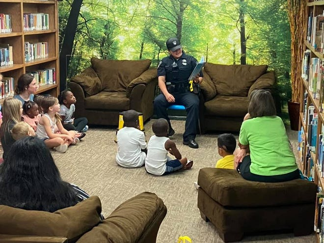 """Stephenville Police Officer Maureena Salazar spends part of her Friday morning reading """"Duck! Rabbit!"""" by Amy Rosenthal as part of Books with the Blue at the Stephenville Public Library."""