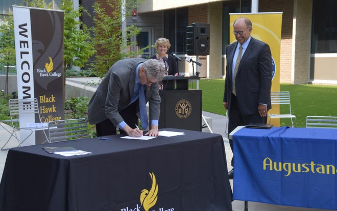 Black Hawk College President Tim Wynes signs the articulation agreement between Black Hawk College and Augustana College.. He is flanked by Steven Bahls, president of Augustana College, and Dr. Amy Maxeiner, vice president for instruction at Black Hawk College.
