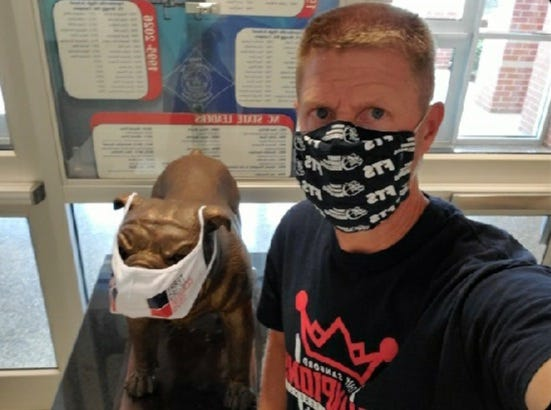 Tom Hatch, principal of Terry Sanford High School in Fayetteville, says his recent tweet on masks in schools was to make sure students and parents knew where he stood. 'The delta variant has hit home,' he said and stressed that masks are a way to keep students safe as they return to school later this month. Behind him, also wearing a mask, is a statue of the school mascot, a bulldog.