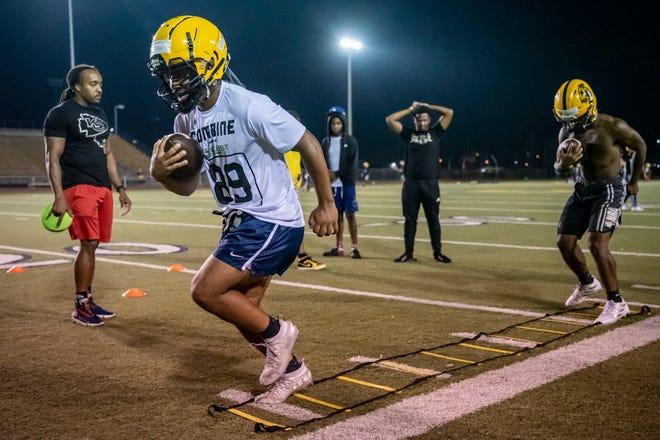 Battle Creek Central senior Asael Adon and junior Kailan Brown run drills on Monday, Aug. 9, 2021 at C.W. Post Stadium in Battle Creek, Michigan.