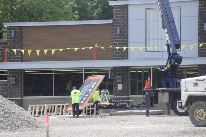 Workers move the Aldi sign outside the new Bucyrus location Monday morning.