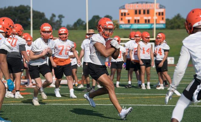 Cherokee's Brandon Boria, center, runs the ball during Cherokee's first football practice of the season at Cherokee High School in Evesham Township on Monday, August 9, 2021.