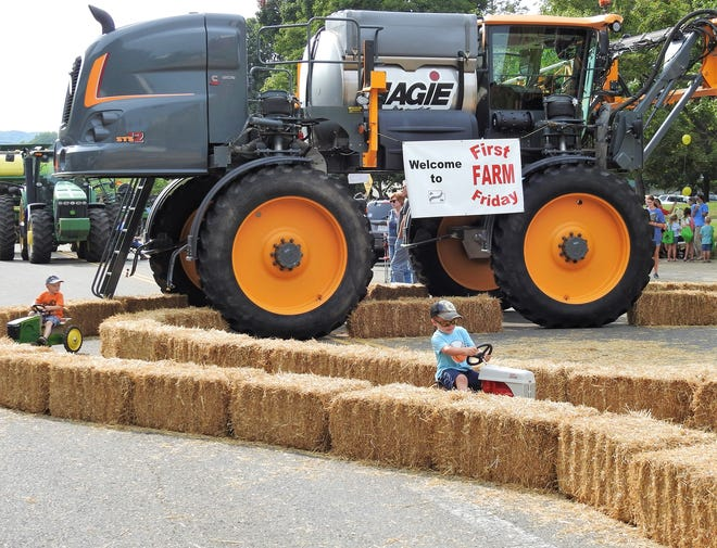 Children ride a pedal tractor through a corn maze in front of a large piece of farm machinery at the First Farm Friday event on Main Street. The focus of the event was to education youth on Coshocton County's deep agricultural roots.