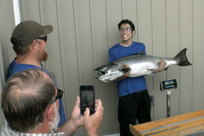 In a photo from Saturday, Aug. 7, 2021, Louis Martinez, 19, of Ortonville, holding a new Michigan state record Chinook salmon, smiles as he looks over to Icebreaker Charters Capt. Bobby Sullivan, top left, outside Captain Chuck's II in Ludington, Mich. Martinez and his family chartered with Sullivan and caught the 47.86-pound, 47½-inch Chinook salmon off of Big Sable Point on Lake Michigan.