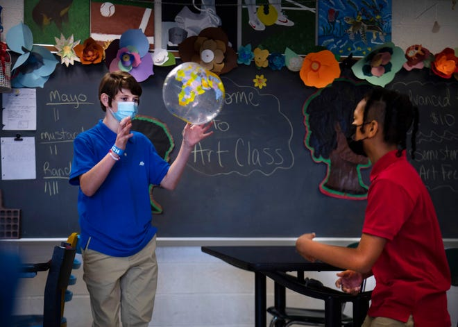 Seventh-grader Aiden Green, right, tosses an inflatable ball to Dawson Alverson while calling out his name in Jeslyn Schiele's art class at Plaza Park Middle School Monday morning, Aug. 9, 2021. The game was a way for the kids to learn each others names on the first day of school.