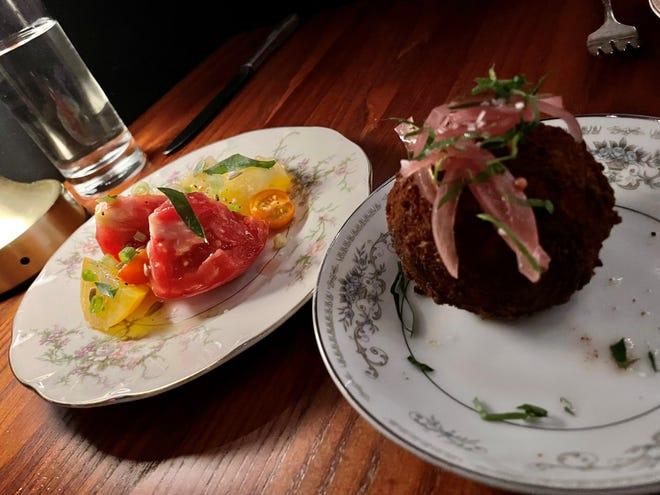 L'arancino osteria stella, a destra, è un impasto fritto a forma di palla a base di riso, ragù, piselli, mozzarella e cipolle sott'aceto.  Sulla sinistra è presentata una selezione di pomodori cimelio.