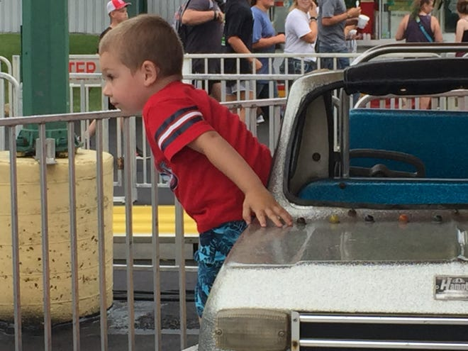 Bryar Hardman, 3, disembarks from a ride Monday evening at the Richland County Fair.