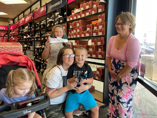 Charlie Hill with her son Charles Hill, 4, sitting on her lap showing off his new pair of shoes alongside his sister Hailee Hill, 9, who also got a new pair of shoes on Monday.
