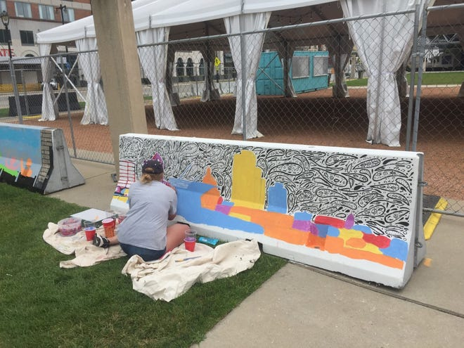 Caroline Ferrero, a Milwaukee Institute of Art and Design student, paints one of the concrete barricades recently installed as part of the Marcus Performing Arts Center's enclosure of the former tree grove to create additional space for paid events.