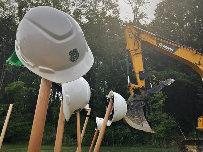 Hardhats worn by school leaders and elected officials sit at a groundbreaking event for a new building on Columbia State Community College's Williamson campus.
