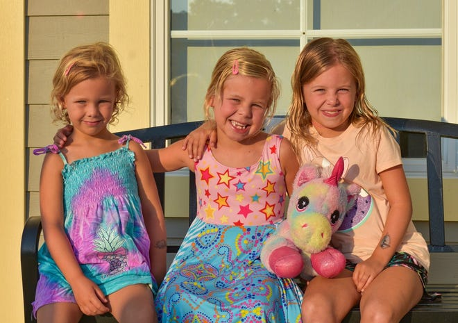 Natalie, Zoe and Molly Carrigg (left to right) sit outside the Marblehead Peninsula Branch Library after leaving their stuffed animals inside for a sleepover. The girls were looking forward to returning the next morning to hear about the party.