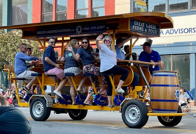 People ride on pedal pub Great Lakes Pedal & Pour during the Rotary International Day Parade on July 21, 2021.