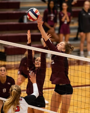 Lauren Murphy, right, blocks a shot for Round Rock against Lake Travis on Monday. Round Rock won a nondistrict volleyball match at home over Lake Travis in five sets in the season-opener for both teams.
