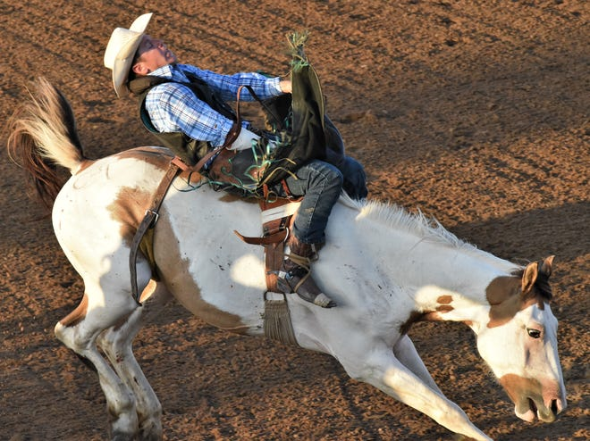 Tony Tharp, 37, holds on during the bronc competition at the Bastrop Homecoming Rodeo on Saturday.