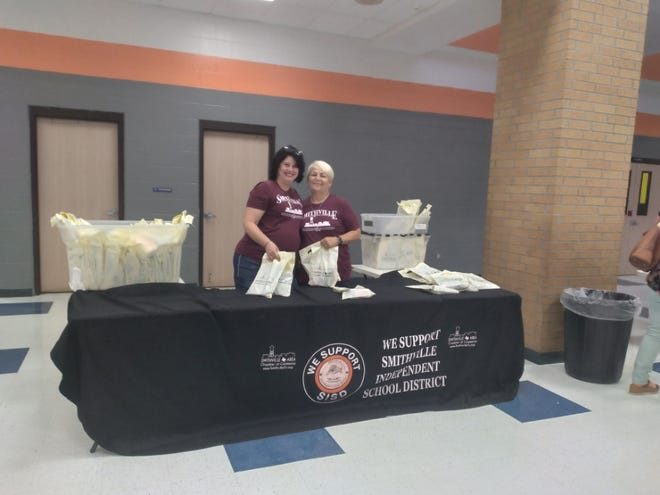 Cory Kadlecek and Bridgette Padgett hand out goodie bags to Smithville school district employees at the 2021 Convocation.