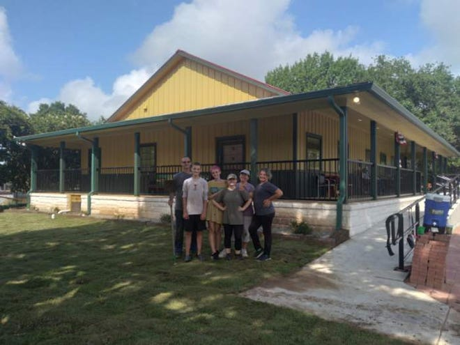 Steve Schroeder and his team pose on the newly installed lawn of the new chamber of commerce and museum building