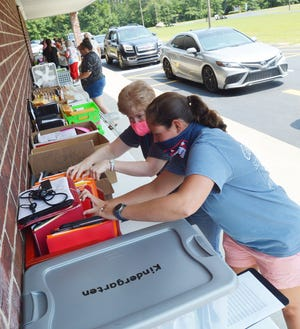 Glascock County teachers and staff provide laptops, packets and books for the waiting line of students and parents who drove through the bus loop Tuesday, Aug. 10. The school is switching to a virtual model for at least two weeks after an outbreak that led to multiple students and teachers testing positive and more than 100 having to quarantine because of exposure.