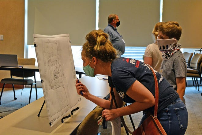 Melanie Hynek and her son, Gideon, look at preliminary plans Monday of the new Columbia Fire Department station planned for Scott Boulevard, north of Montauk Court, in southwest Columbia.