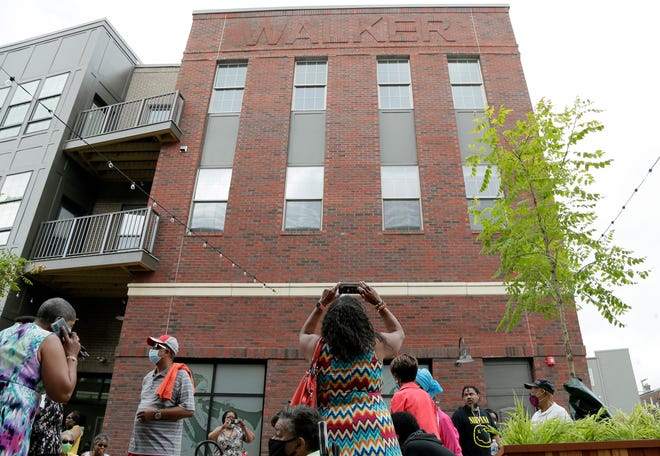 """A woman takes a photo of the name """"Walker"""" while standing in the new Ann B. Walker Plaza, part of an apartment complex along East Long Street, dedicated on Tuesday. Walker is a Black broadcasting pioneer and community leader now in her 90s who served in the Carter administration."""