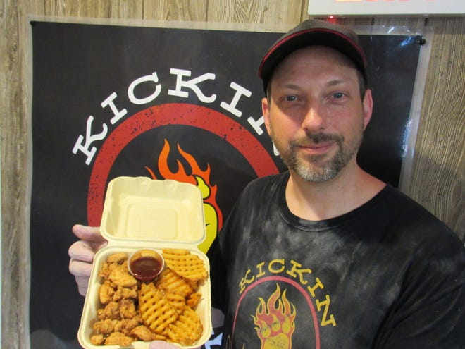 Michael Venne holds up a combo of chicken tenders and waffle fries at his business, Kickin Chicken Mobile, 5413 Sinclair Road. He parked his food cart and has struggled to find footing during the COVID-19 coronavirus pandemic but said business is rebounding.