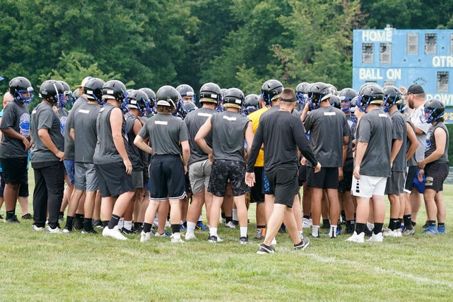 The Madison football program gathers on the field during Monday's practice.