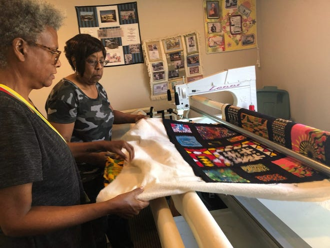 Quilters Lauren Austin, left, and Marva Sloan, work on one of the quilts on a long-arm sewing machine.