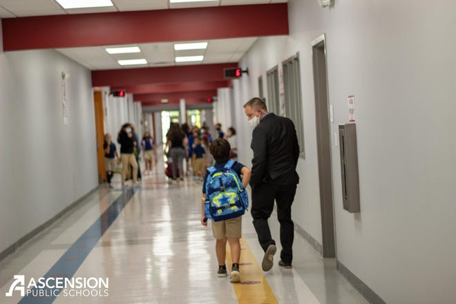 Ascension Parish Schools Chief Operations Director Chad Lynch walks with a student down the hallway at the newly-opened Sugar Mill Primary School on Germany Road.