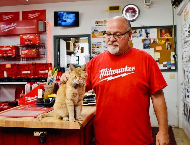"Dave Beasley alongside shop cat ""Lil Foot""."