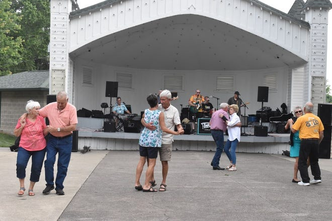The Tailfins perform on stage in the historic bandshell in Central Park, Orion, while couples dance during Main Street Orion's Cruise In to Orion on Saturday, Aug. 7.