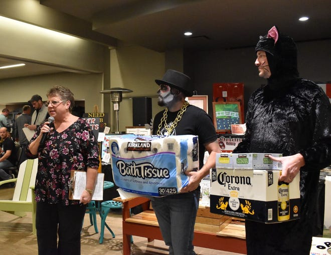 The coronavirus pandemic inspired the first package offered during the live auction at the Orion Educational Foundation's Spring Gala on Friday, March 13, 2020. at the Camden Centre, Milan. While auctioneer Jana Stenzel, left, calls for bids, Derek Engstrom, center, holds 30 rolls of toilet paper and Neal Nelson displays a case of Corona beer and a box of exam gloves. When people realized they might have to stay at home during the pandemic, they bought all the toilet paper they could find in stores. This year's Spring Gala was postponed until Saturday, Aug. 21. Festivities begin at 5:30 p.m. in Central Park.