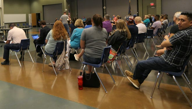 The crowd applauds when parents address the Hutchinson School Board about reconsidering a mask mandate for all students.