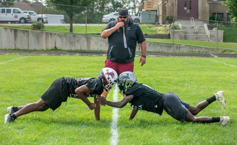 Peoria High coach Tim Thornton watches as a pair of his players compete to knock each other over from the push-up position during practice this month at Peoria High School.