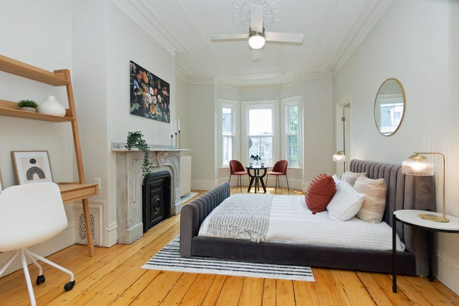The primary bedroom in Unit 2 has natural light streaming in through bay windows. The ornamental marble fireplace surround is the highlight of the room.