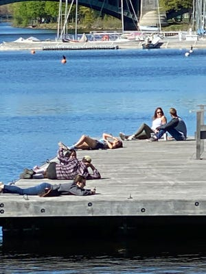 These people are enjoying a fine day by the Charles River along the Esplanade.