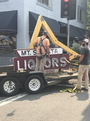 Workers from McHale Signs in Redding carefully removed the Mt. Shasta Liquors sign on Aug. 4, 2021 from the building at the corner of Mt. Shasta Boulevard and Lake Street.