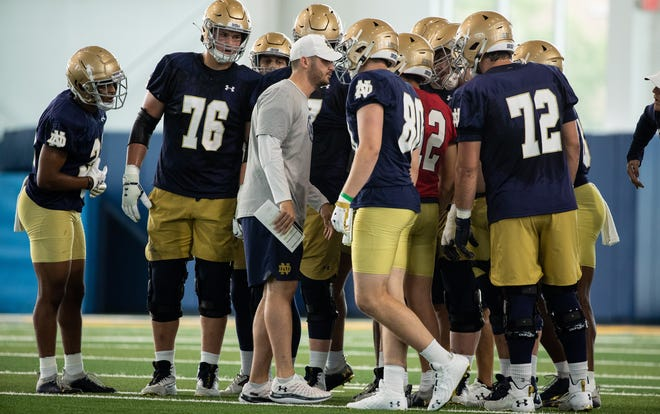 Notre Dame offensive coordinator Tommy Rees  (center) missed practice Tuesday after undergoing an appendectomy Monday night.