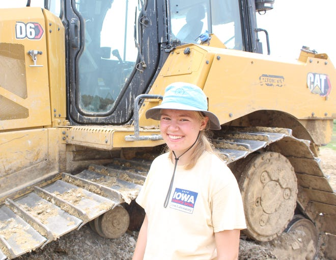 Brown University student Eliana Hornbuckle pictured next to CAT D6 at the Tama County Landfill. Hornbuckle spent a day with Kevin Cooper to learn about agriculture and farming. Part of the day included cleaning up from the 2020 derecho storm damage.
