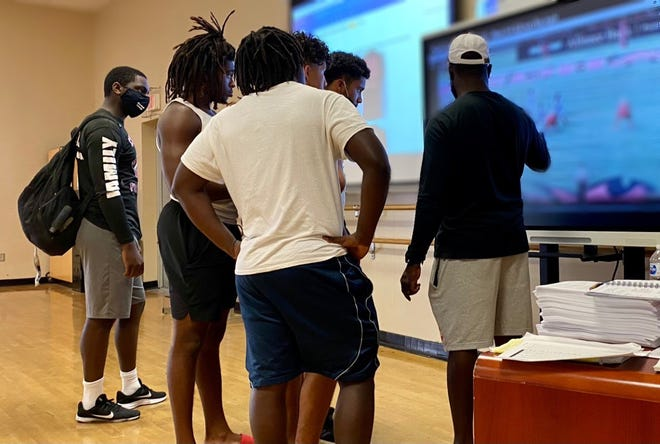 Masks on, members of Palm Beach Central's football program review film with an assistant coach to learn what plays they'll be calling for the 2021 season.