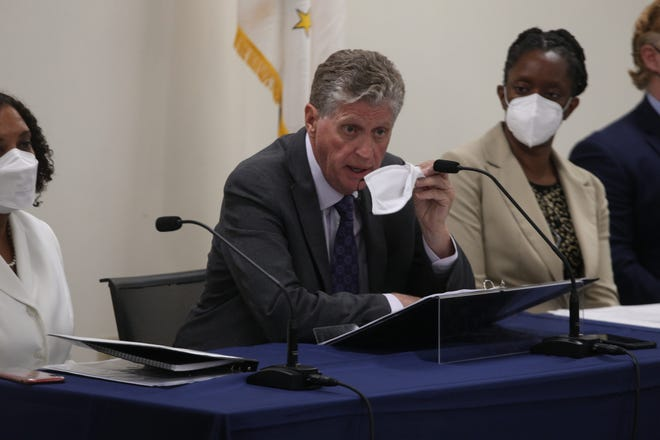 Gov. Dan McKee shows the mask that he carried with him into the Tuesday afternoon news conference. At right is state Health Director Dr. Nicole Alexander-Scott.